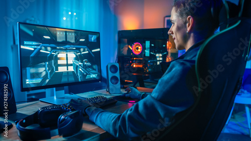 Photo Happy Gamer Playing First-Person Shooter Online Video Game on His Powerful Personal Computer