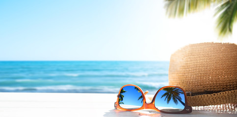 Sunny tropical beach vacation background; glasses and palm tree reflex