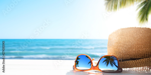 Photo  Sunny tropical beach vacation background; glasses and palm tree reflex