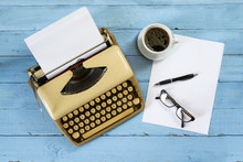 Old Beige Typewriter From The 1950s With Paper, Coffee And Glasses On A Blue Painted Wooden Table, High Angle View From Above