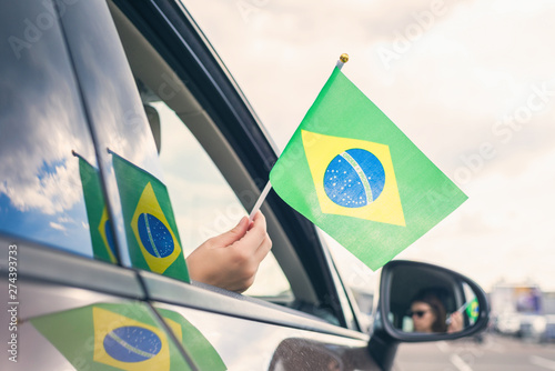 Foto  Woman or Girl Holding Flag of Brazil from the open car window