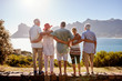 canvas print picture - Rear View Of Senior Friends Visiting Tourist Landmark On Group Vacation Standing On Wall