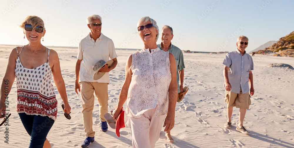 Fototapety, obrazy: Group Of Senior Friends Walking Along Sandy Beach On Summer Group Vacation