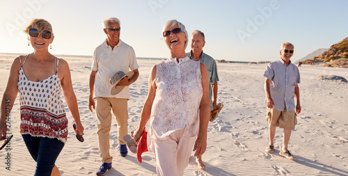 Foto  Group Of Senior Friends Walking Along Sandy Beach On Summer Group Vacation