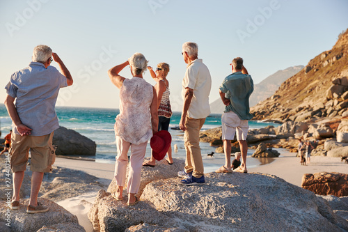 Foto  Rear View Of Senior Friends Standing On Rocks On Summer Group Vacation Looking O
