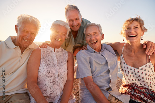 Foto  Portrait Of Senior Friends Sitting On Rocks By Sea On Summer Group Vacation