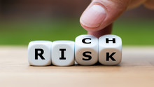 """Take A Risk And Getting Rich Concept. Hand Turns Dice And Changes The Word """"RISK"""" To """"RICH""""."""