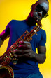 canvas print picture Young african-american jazz musician playing the saxophone on yellow studio background in trendy neon light. Concept of music, hobby. Joyful attractive guy improvising. Colorful portrait of artist.