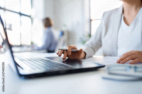 business and people concept - businesswoman with laptop computer and papers working at office