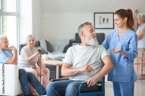 Cuadros en Lienzo Elderly man with caregiver in nursing home