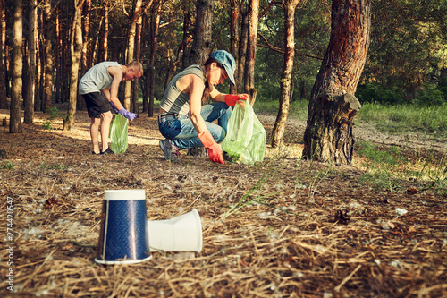 Young  girl picking up the garbage and putting it in a garbage bag on a natural background Fototapeta