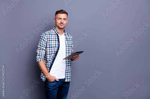 Portrait of his he nice attractive content cheerful calm bearded grey-haired guy wearing checked shirt holding in hand e-book isolated over blue violet pastel background