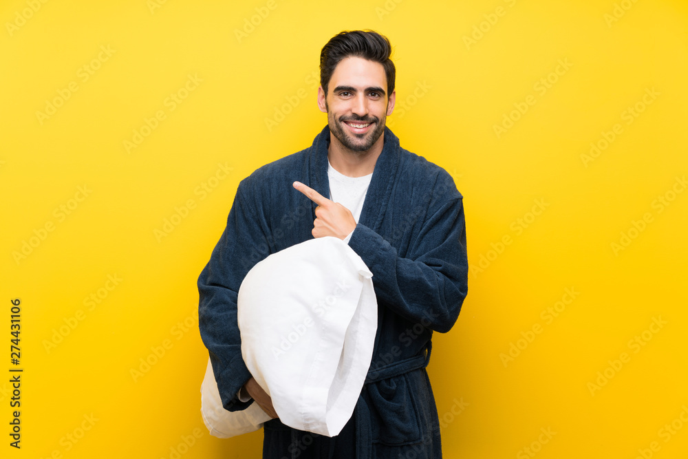 Fototapety, obrazy: Handsome man in pajamas pointing to the side to present a product