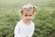 Little Baby Girl With Blond Hair And Two Tails, Wearing A White T-shirt Standing On Green Grass In Nature, Smiling