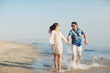Happy Couple Walking And Playing On The Beach, Soaking His Feet In The Water. Wonderful Love Story In Rimini, Italy