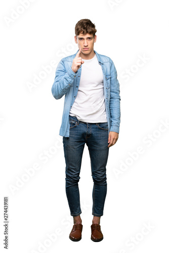 A full-length shot of a Handsome young man frustrated and pointing to the front over isolated white background Wall mural