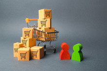 Shopping Cart With Cardboard Boxes With A Pattern Of Trading Carts A Buyer And Seller, Manufacturer And Retailer. Business And Commerce. Negotiations On Supply Of Goods, Purchase Of Goods And Services
