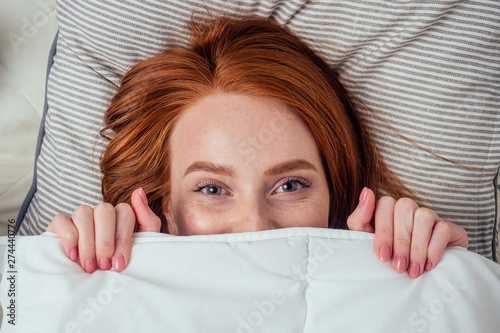 Photo caucasian beautiful redhaired ginger woman hidden under white duvet looking at c