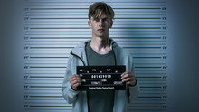 In A Police Station Arrested Drug Addict Teenage Posing For A Front View Mugshot. He Is Heavily Bruised. Height Chart In The Background.