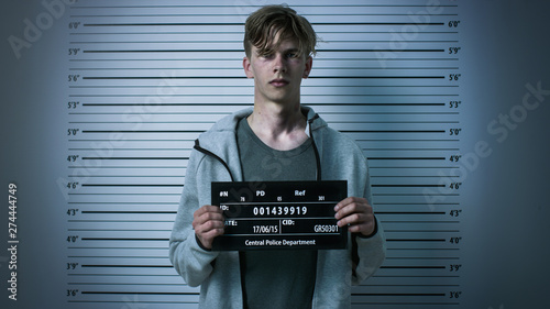 Foto In a Police Station Arrested Drug Addict Teenage Posing for a Front View Mugshot