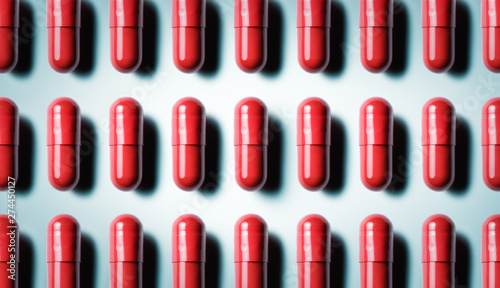 Fotografia  Rows of red capsules on blue grey background