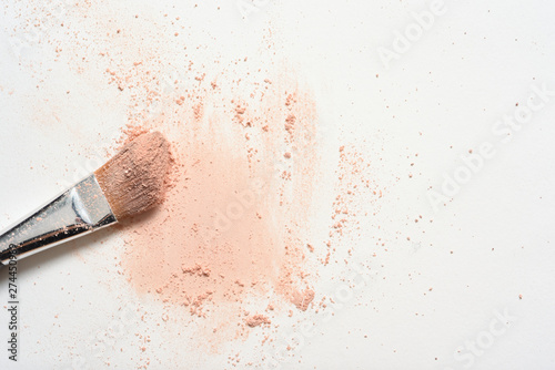 Obraz Pink make up spilled over white surface with make up brush covered in powder - fototapety do salonu