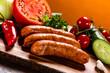 Leinwandbild Motiv Raw sausages and vegetables on cutting board