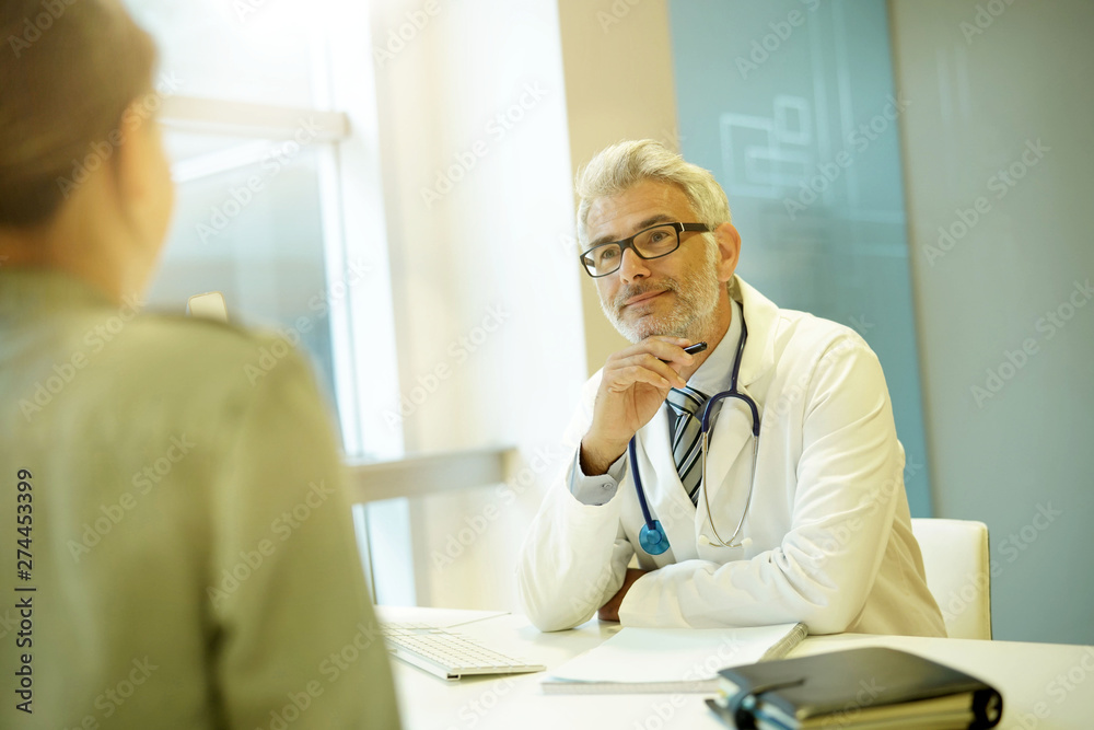 Fototapety, obrazy: Mature doctor talking to patient in modern clinic