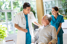 Young Doctor Talking With Patient In Nursing Home