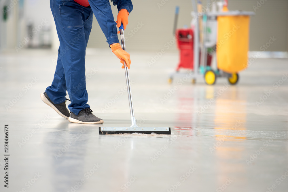 Fototapety, obrazy: The man in the repairman is holding a mop in a white suit, cleaning the protective clothing of the new epoxy floor in an empty warehouse or car service center.