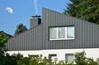 canvas print picture - Fassaden- und Schornstein-Verkleidung eines modernen Wohngebäudes aus dunkelgrau beschichtetem Stehfalz-Metall und Fenster mit Sichtschutzstreifen,