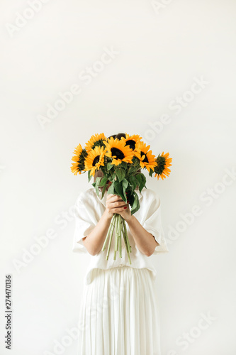 Young pretty woman in white dress hold sunflowers bouquet on white background. Florist minimal concept.