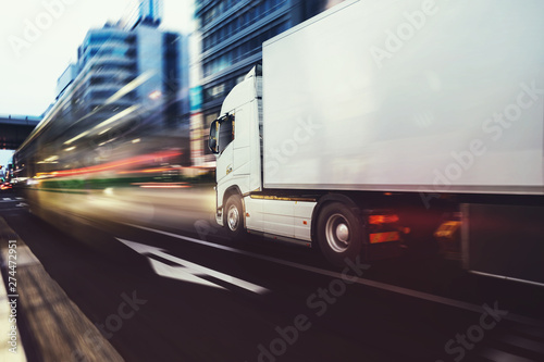 White truck moving fast on the road in a modern city with light effect Fototapet