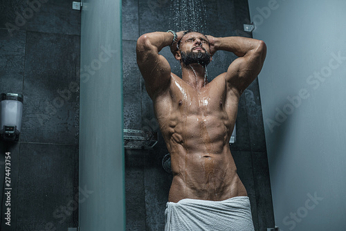 Sexy muscular man with naked torso in shower. Bodybuilder. Mature content - 274473754