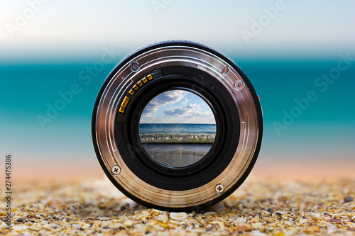 Obraz View of the sea surf through a photographic lens lying on a sandy beach on a sunny day. - fototapety do salonu