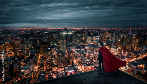 Fotografía  Businessman with red cape like a superhero standing on the rooftop and looking a