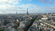 Aerial, tracking, drone shot, of the Eiffel tower, overlooking traffic on french streets, buildings and architecture, in the city of Paris, on a sunny, summer day, in France