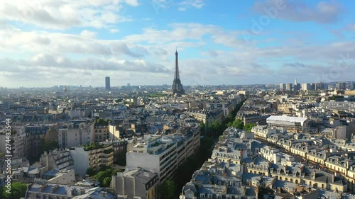 Aerial, tracking, drone shot, of the Eiffel tower, overlooking traffic on french streets, buildings and architecture, in the city of Paris, on a sunny, summer day, in France - 274483544