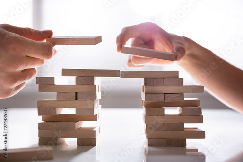 Photographie Human's Hand Placing Wooden Block