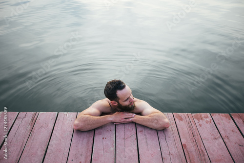 Man relaxing and swimming in the lake or a wimming pool Wallpaper Mural