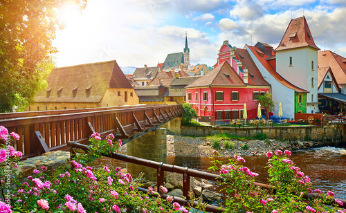 Obraz Czech Krumlov, (Cesky Krumlov), Czech Republic. Wooden bridge over river Vltava. Vintage picturesque old town with colorful houses and chapel of church. Rose flowers on bank. Sunny summer day. - fototapety do salonu