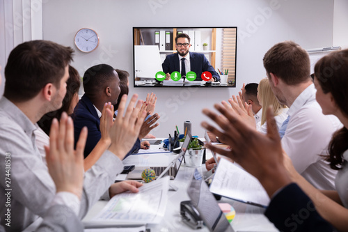 Businesspeople Having Video Conference In Boardroom - 274488538