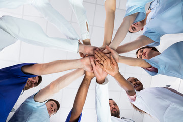 Directly Below Shot Of Doctor Stacking Hands Together