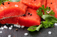 Fresh Raw Pacific Wild Sockeye Salmon Fillets On Natural Stone With Spices And Basil Leaves