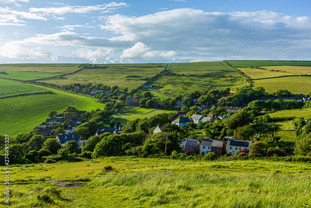 Fototapeta A view of a rural village (West Lulworth) from the hill under a majestic blue sky and some white clouds