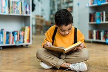 Cute African American Boy Sitting On Floor And Reading Book