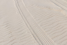 Tire Trail In The Sand Of Dunes On The Beach Or Desert.