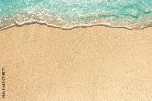 Carta da parati Soft waves with foam of blue ocean on the sandy beach