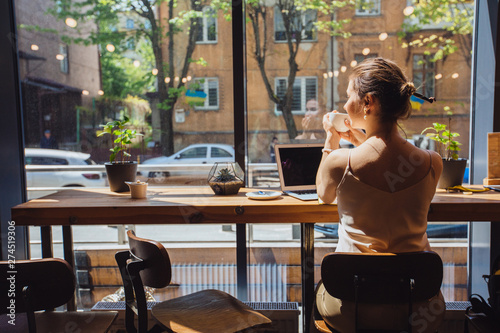 Caucasian romantic woman blogger relaxing drinking tea while sitting near the window in modern loft cafe bar,female freelancer thinking about new ideas during work on laptop computer. Copy space