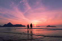 Two Lovers Standing Together On A Tropical Beach,  Beautiful Sunset In The Background